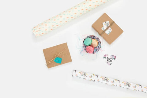 5 Tips for a fuller life + Present + JWLRY + White table with presents, wrapping paper and colorful macrons in a basket.