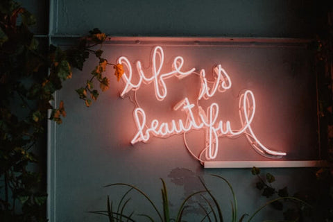 """5 tips for a fuller life + Grateful + JWLRY + """"Life is beautiful"""" pink neon lights hanging on wall next to a plant."""