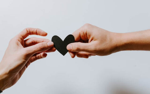The power of words + Sharing + JWLRY + two hands holding up a small, black, paper heart.
