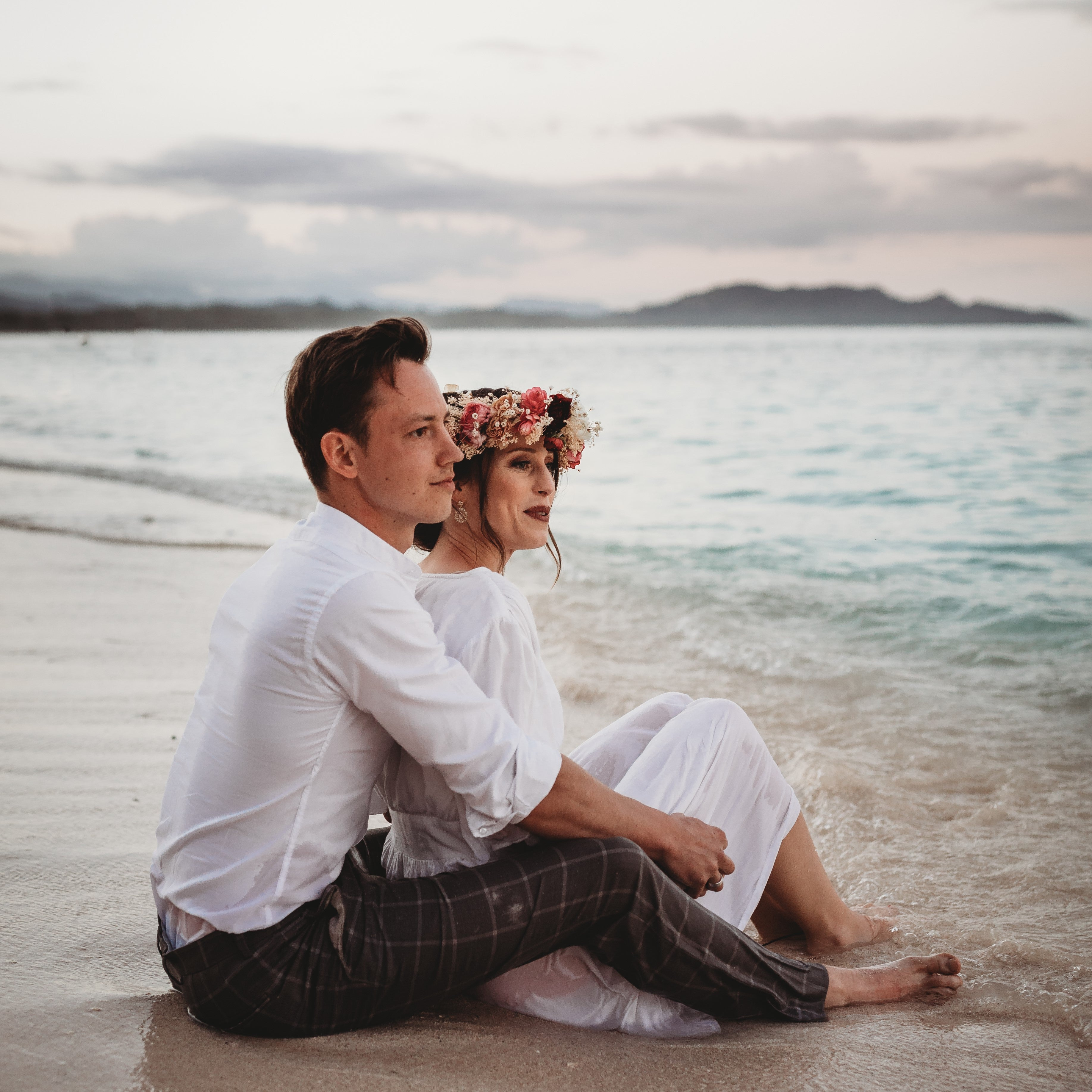 JWLRY CEO Amber Buyse sitting on the beach in Oahu Hawaii with husband Thomas.