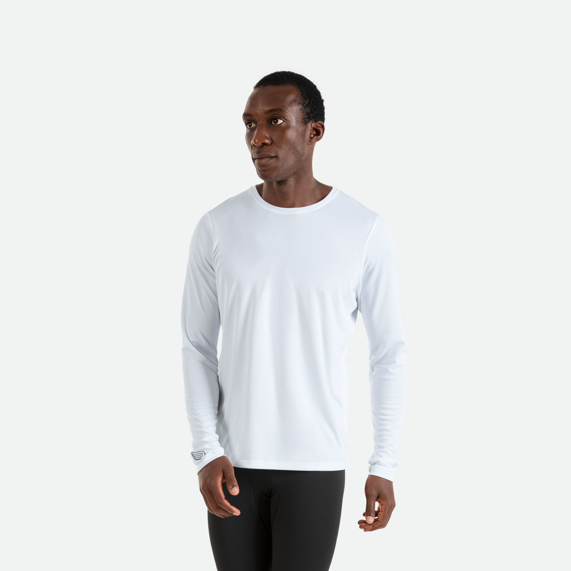 Our Pressio men's white Hāpai long sleeve t-shirt features EcoTECH MF fabric which has dual filament recycled polyester yarns from Unifi for superior moisture control to keep you dry.