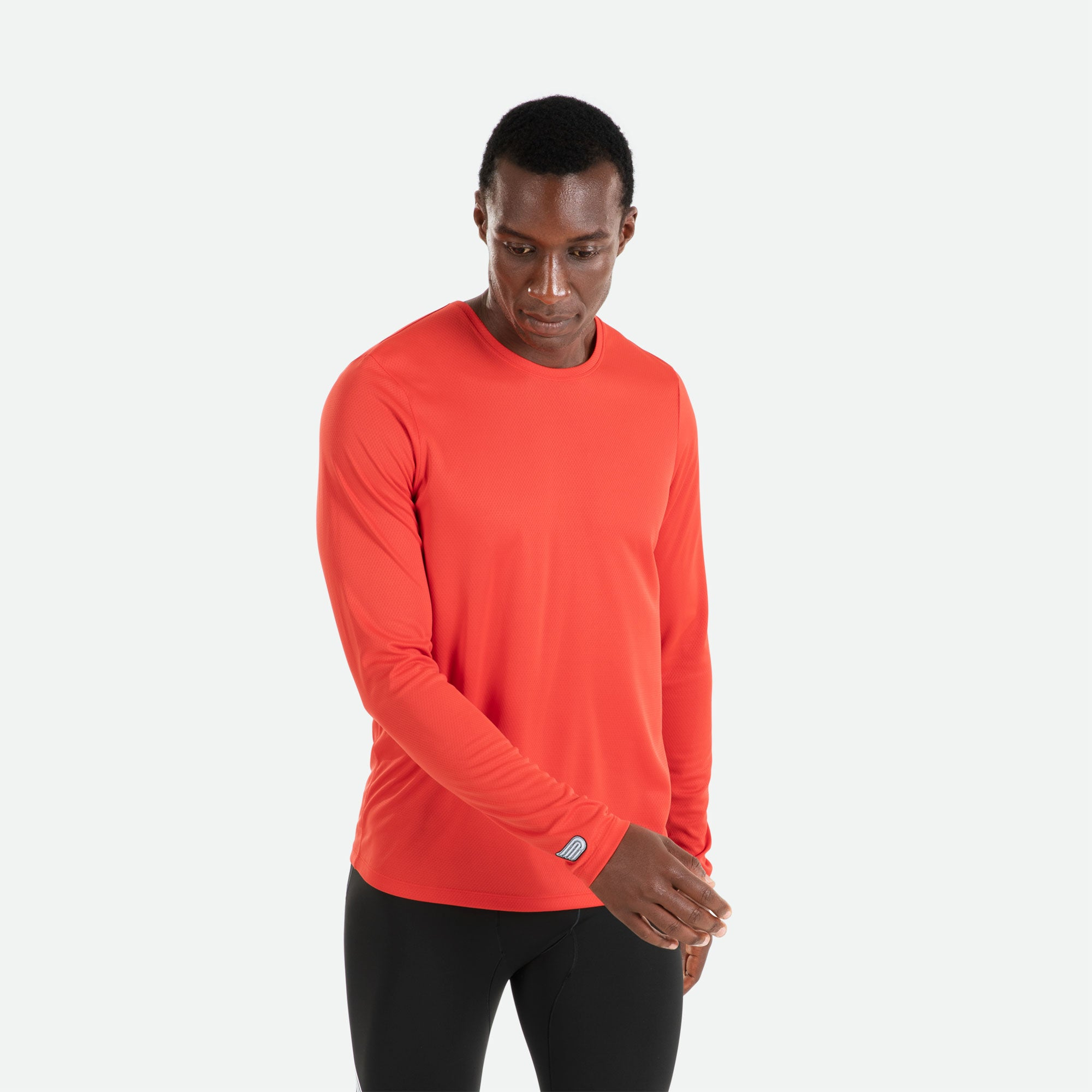 Our Pressio men's red Hāpai long sleeve t-shirt features EcoTECH MF fabric which has dual filament recycled polyester yarns from Unifi for superior moisture control to keep you dry.