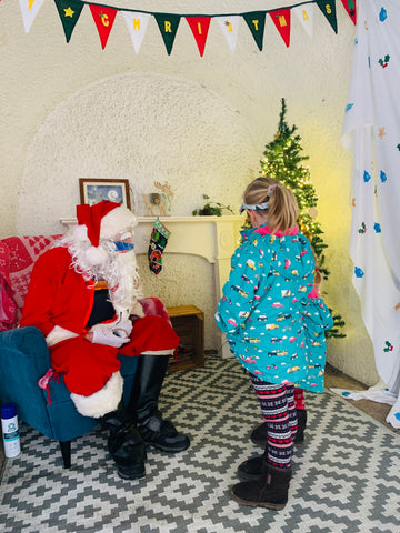 Two girls meet Father Christmas at the Readymoney Cove Grotto in Fowey