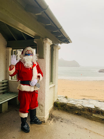 Father Christmas standing under the shelter at Readymoney Cove, Fowey. He is waving. The sea is in the background.