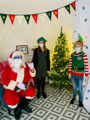 Santa by the Sea at Readymoney Cove, Fowey, Cornwall with his two elves, Isla and Barnaby