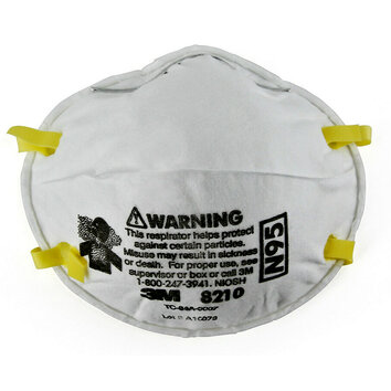 Image of a white N95 mask with a silver nose piece, yellow ear straps, and a warning label printed on the front.