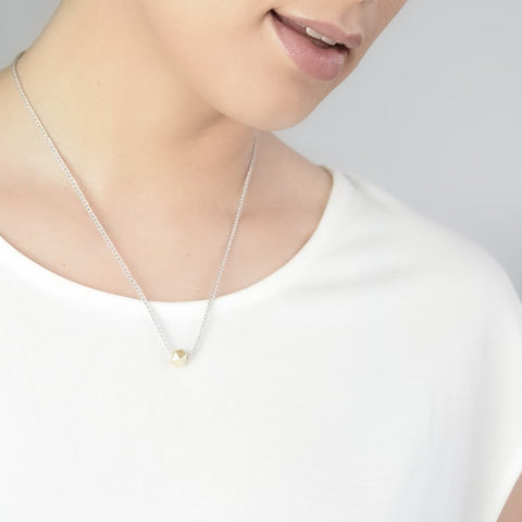 Close up of model wearing silk solitaire necklace.