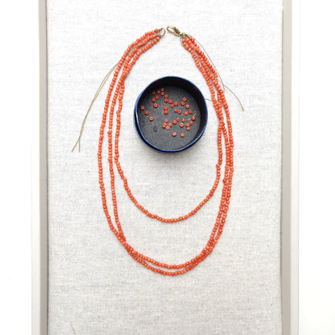 Overview of three-strand coral necklace in need of a restringing.