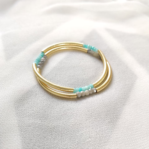 A pair of triplet bangles in amazonite and gray moonstone on ivory crepe silk.