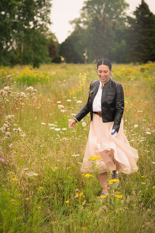 Woman walking through a field of flowers in black leather jacket and pink tulle skirt.