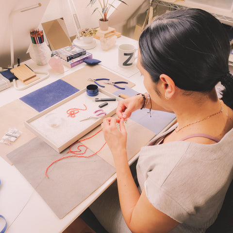 Jewelry designer at the bench fixing the coral necklace.