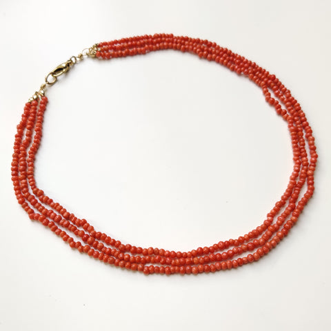 Side overview of the finished three-strand coral necklace.
