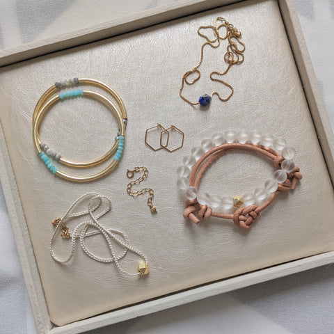 An overview of a selection of gold jewelry in a white tray lined with pearlized vegan leather. One pair of hoops, one necklace extender, two necklaces and four bracelets.