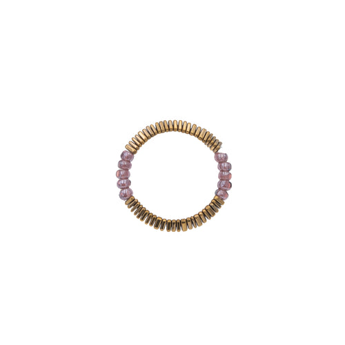 Zurina Ketola Beaded Stretch Ring with Purple Seed Beads and Gold Tiny Triangle Hematite Details on White Background.
