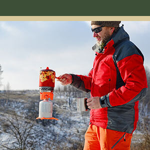 man cooking on jetboil stove in winter
