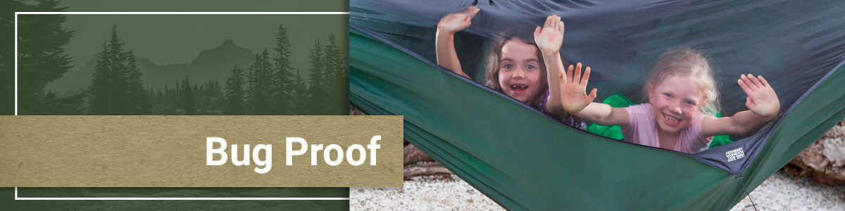 Children smiling through the bug proof netting of a Hennessy Hammock