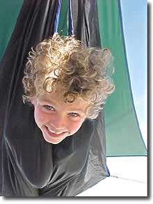 boy sticking head out of hammock