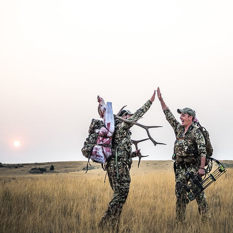 Sitka Gear - two men high fiving at dawn with one of the two men having a recently harvested Elk by compound bow on his back