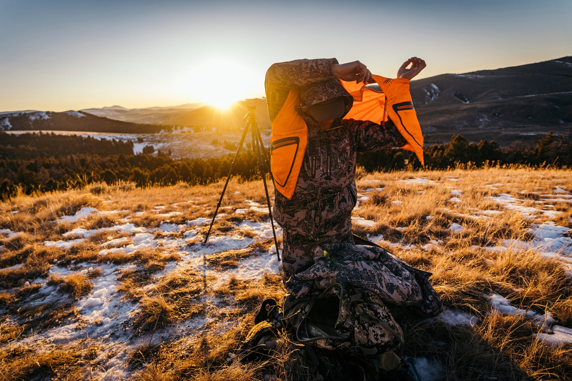 Sitka gear - man knelling putting on a ballistic vest over the Jetstream jacket while the sun rises