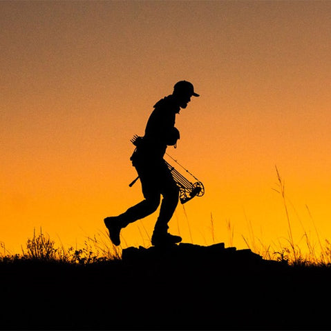 Sitka Gear - Man Running On Ridge with compound bow wearing core lightweight hoody hunting gear