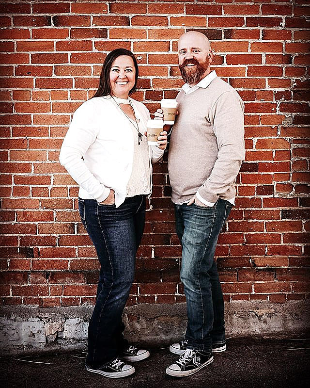 owners, Kim and Donnie in front of a brick wall