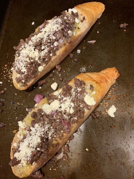 Two slices of bread on a sheet pan topped with elk meat and feta cheese