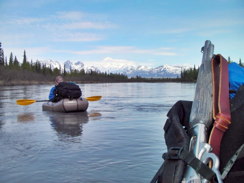 packraft hunting rifle and pack strapped to bow