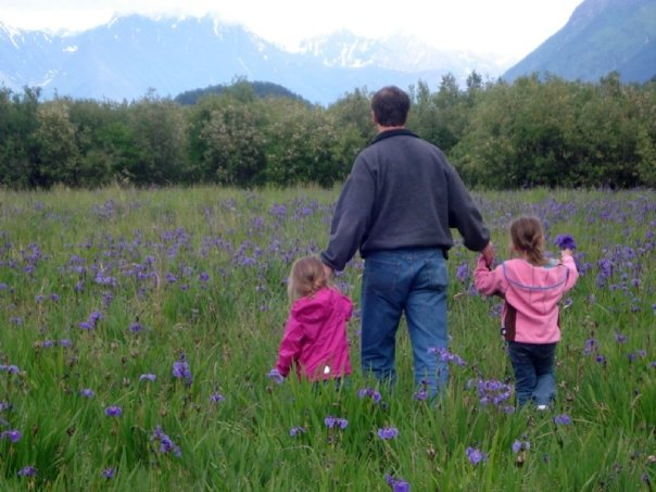 Father with his daughters in a field of flowers