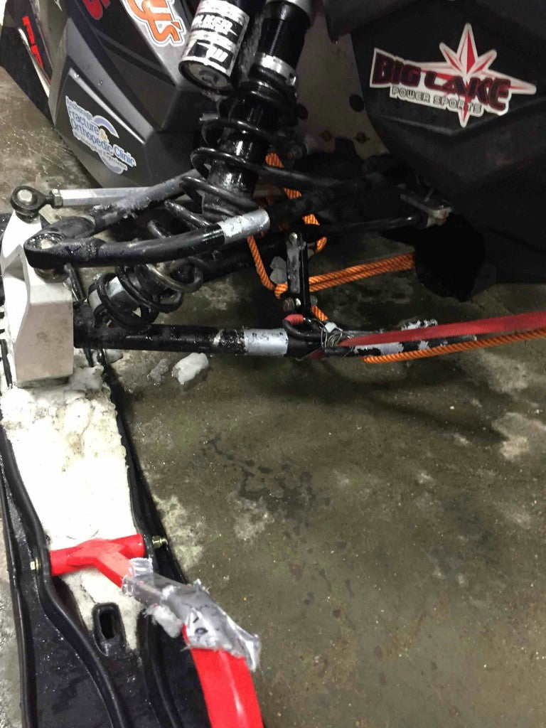 The right side of Ryan Sottasanti's snowmobile showing heavy damage.