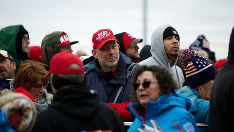 Man wearing a red hat in a crowd