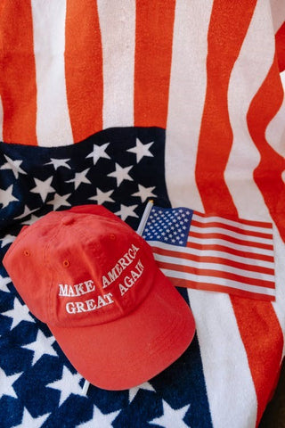 A MAGA hat on top of a US flag