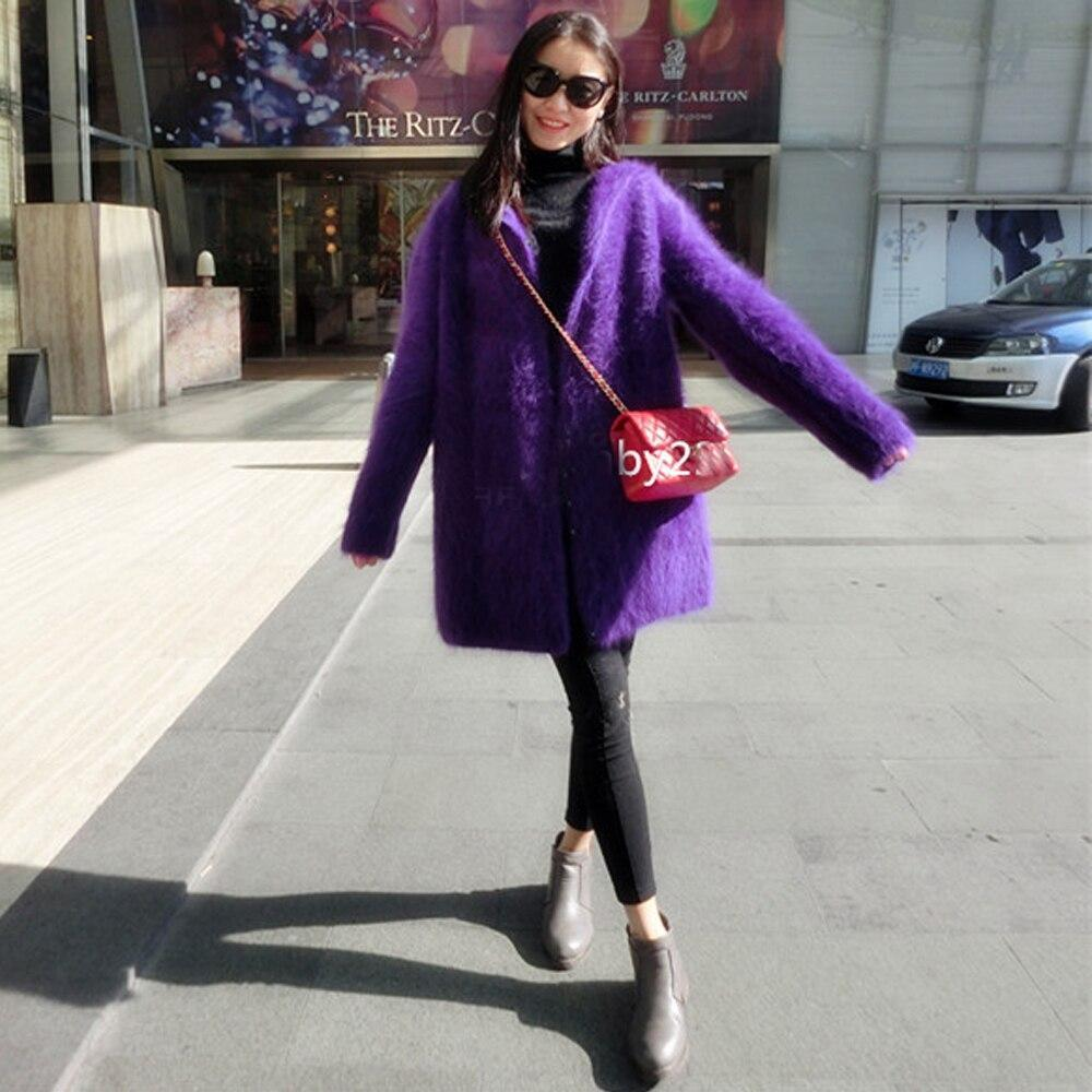 Woman wearing purple coat and blue jeans black sunglasses and red bag