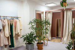 Fitting rooms with a rail of clothes on the left, and potted plants in centre.