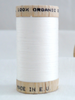 Wooden reel of organic cotton sewing thread in off-white natural colour.