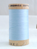 Wooden spool of organic cotton sewing thread in pale blue colour.