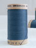 Wooden reel of organic cotton sewing thread in dusty blue, teal colour.