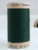 Wooden reel of organic cotton sewing thread in dark green forest colour.
