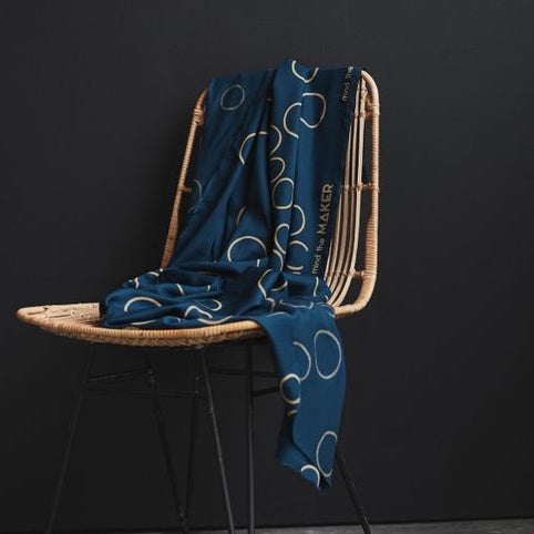 EcoVero Viscose in Ocean Blue with Circle outline prints dotted sporadically. Fabric draped on chair.