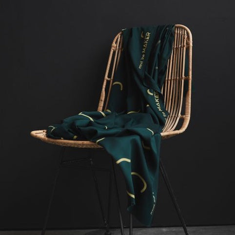 EcoVero Viscose draped over chair. Green fabric with lines prints at random intervals.