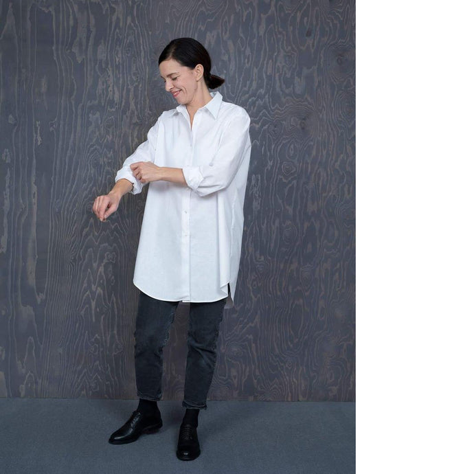 Lady stands wearing an oversized white shirt, rolling up sleeves, worn with ankle length black jeans.