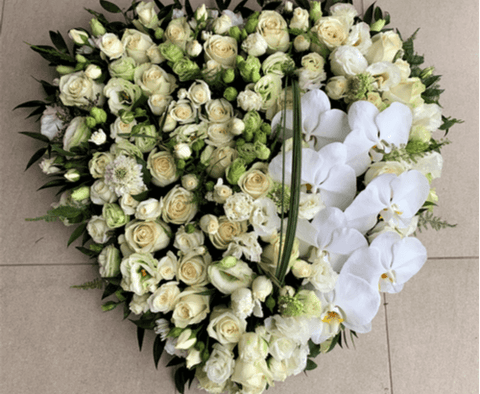 Solid funeral heart wreath with white flowers.