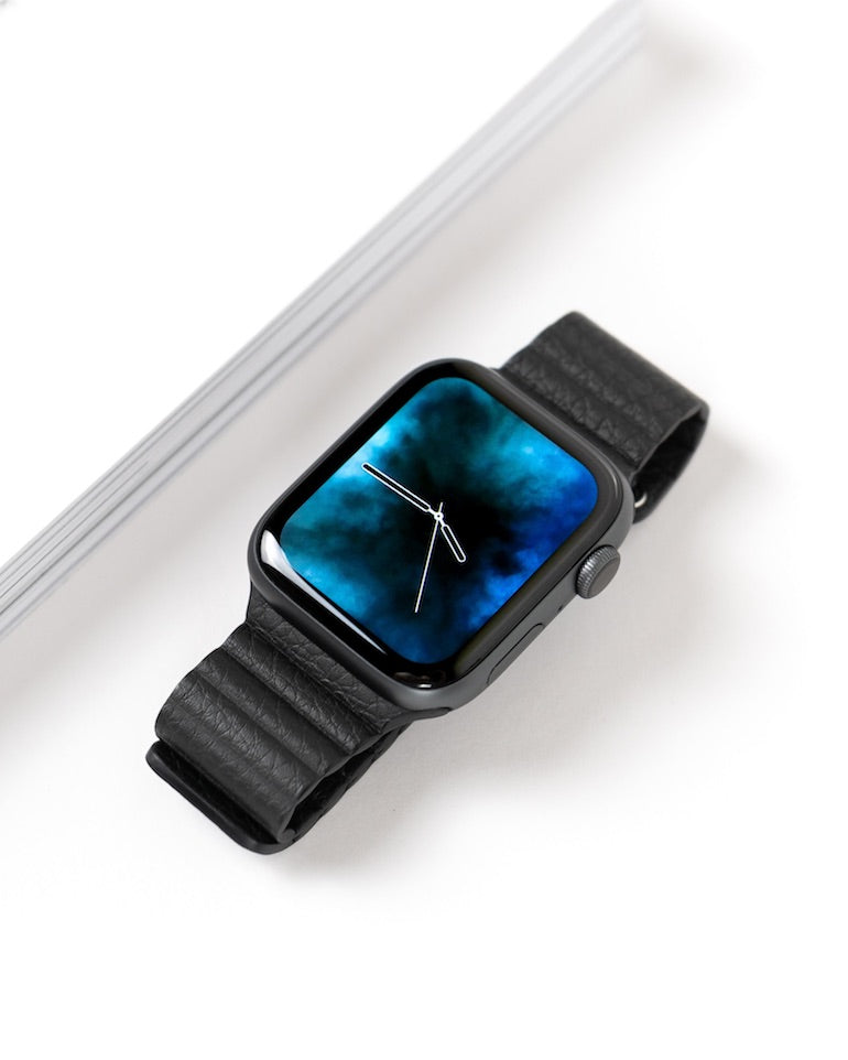 skeuomorphism: still life photo of an Apple Watch with only the hands of a traditional clock visible on its digital screen.