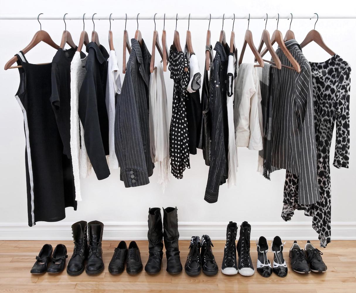 An assortment of black and white clothes hanging on a rack. Black and white shoes neatly lined up underneath the rack.