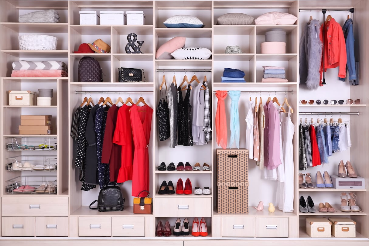 A very organized wardrobe closet with kinds, types, and styles of clothes, shoes and accessories neatly organized in separate compartments.