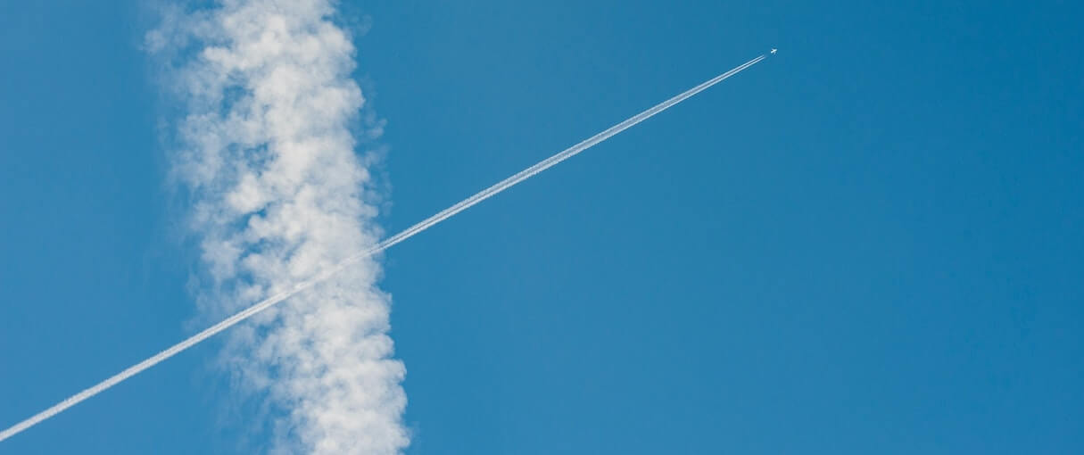 A jet aircraft speeds across a clear sky, leaving contrails in its wake.