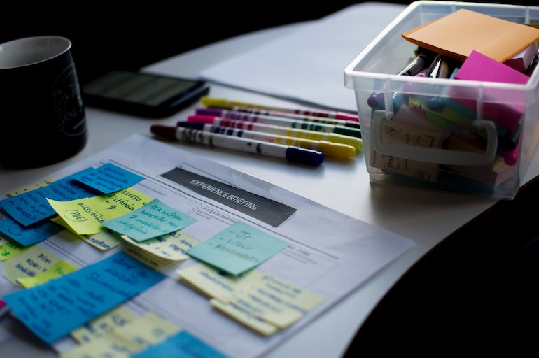 Reply to reviews: A large strategy sheet is covered with colourful post-it notes on a table with a small, clear bucket of markers next to it.