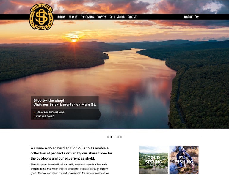 Shopify commerce awards 2020 winners: Screenshot of the Old Souls home page featuring an arial photograph taken by the shop owners of a river surrounded by dense forests at dusk. Text overlaid the photo encourages site visitors to visit Old Souls's brick and mortar shop on Main Street.