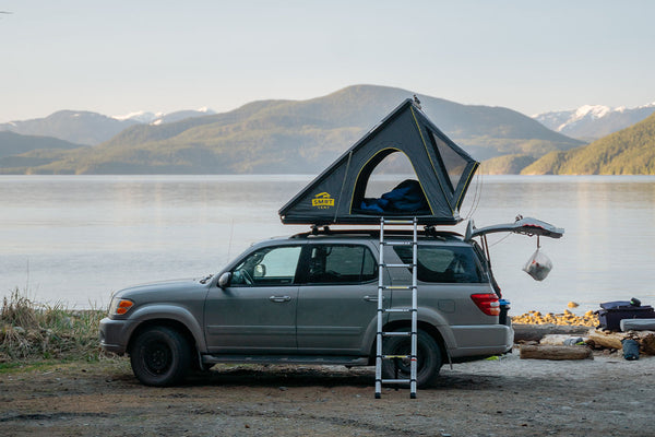 An SUV is parked at the edge of a beautiful lake with a SMRT Tent roof top tent open.