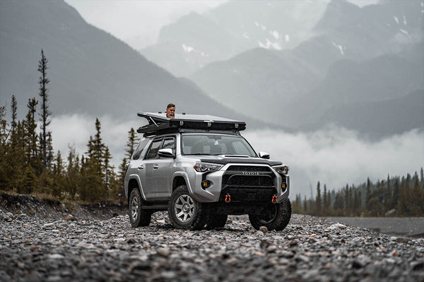 A man opening a SMRT Tent roof top tent on top of his Toyota 4Runner in the mountains.