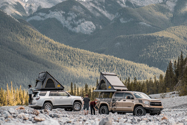 A Toyota Tacoma and a Toyota 4Runner are parked in a valley of mountains with SMRT Tent roof top tents open on top.